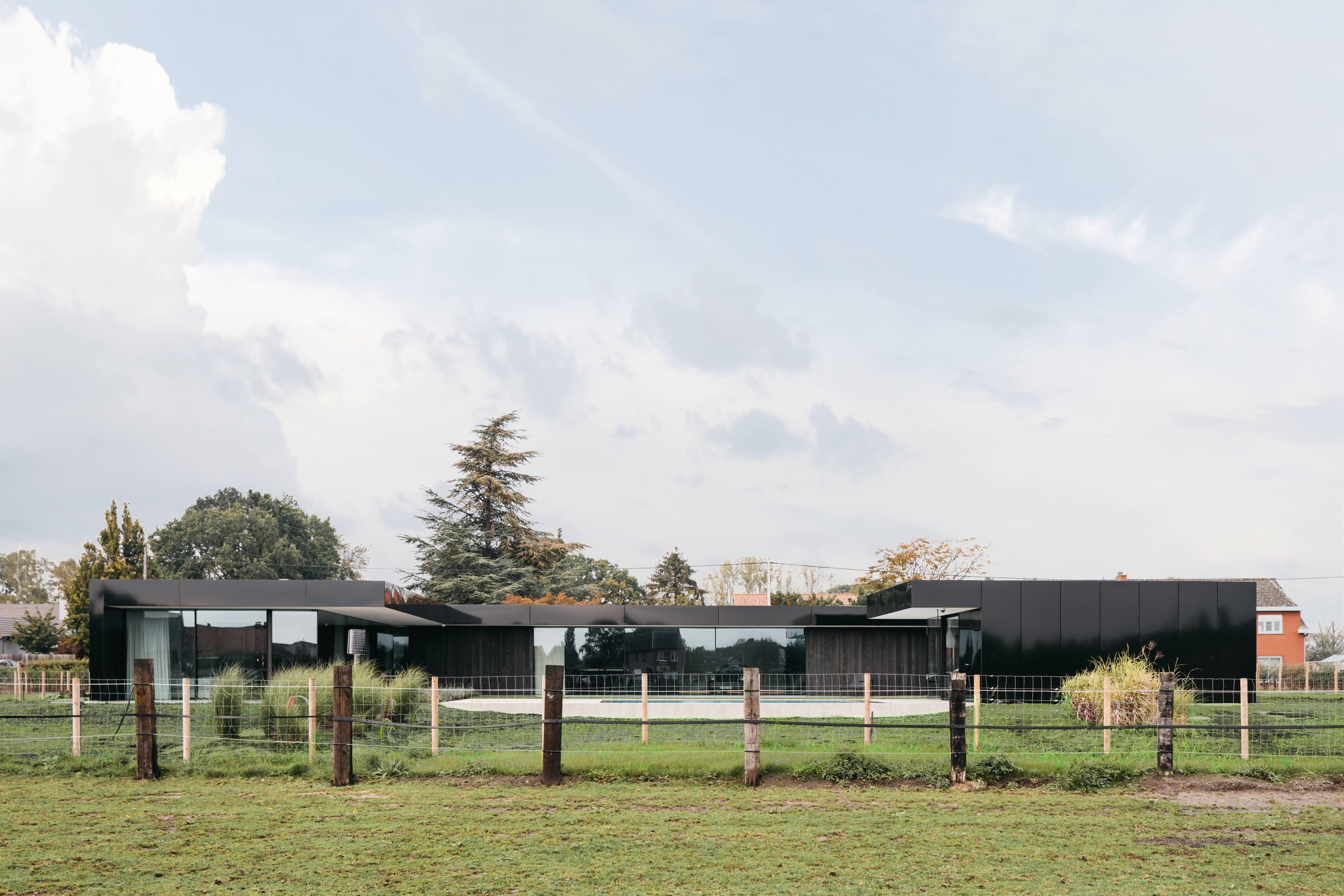 strakke minimalistische woning zwart reflecterend hoogglans panelen grote ramen marmer zwembad autolift porsche gouden windhond sint-katelijne-waver icoon architecten brasschaat